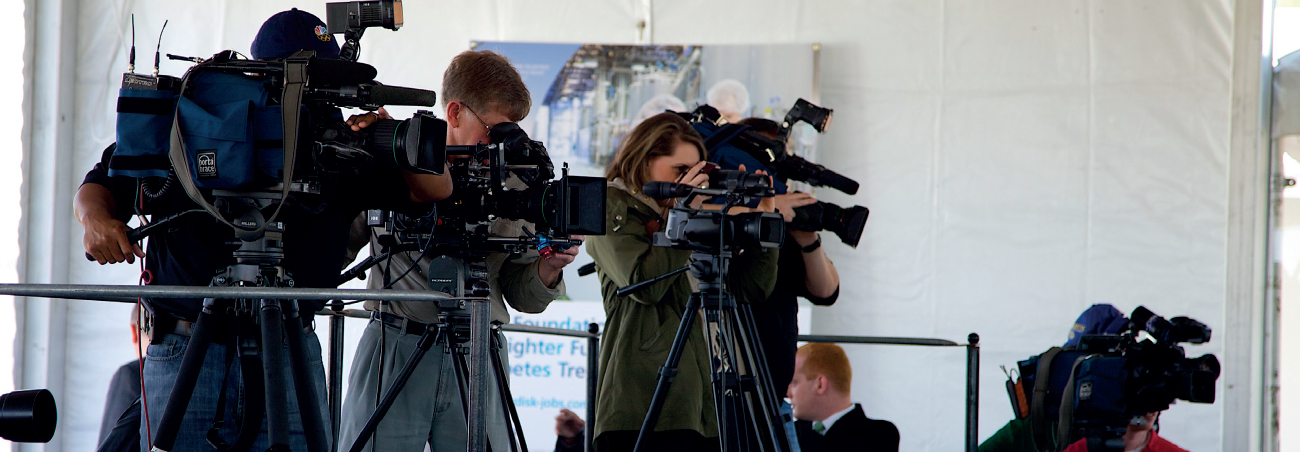 News reporters with cameras filming an event
