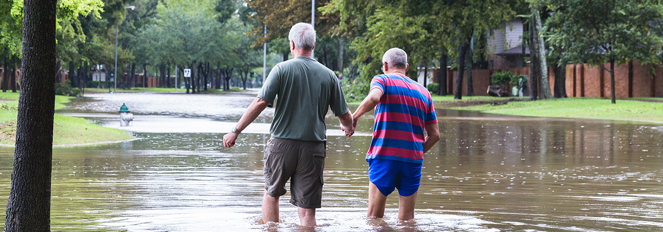Two men walking together through a neighborhood flooded by a natural disaster