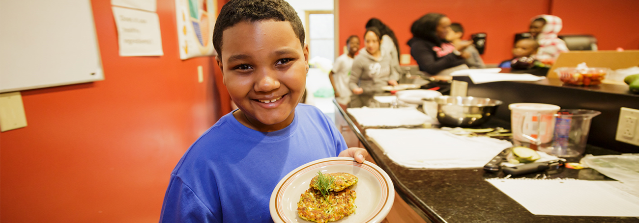 Child holding a plate of healthy food at school cafeteria