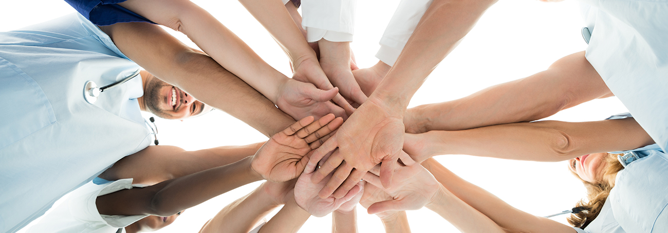 Group of people with their hands together in the middle