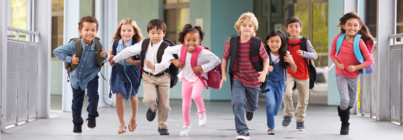 Young students running through a school hallway